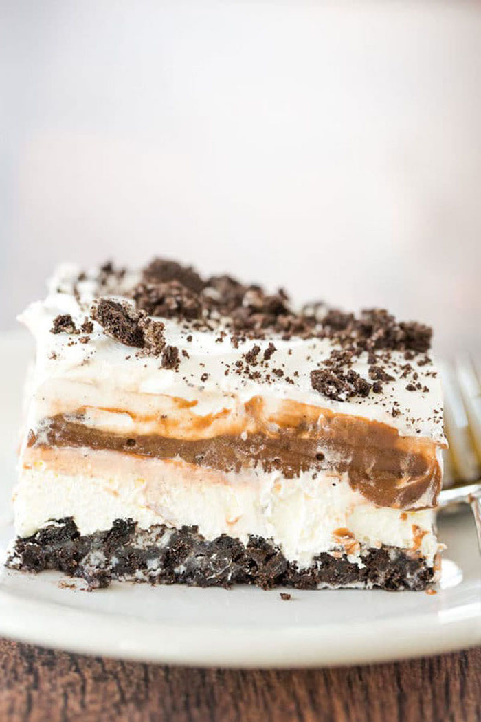 oreo cake, layered with caramel, cookie crumbs on top, on a white plate, wooden table, summer dessert recipes