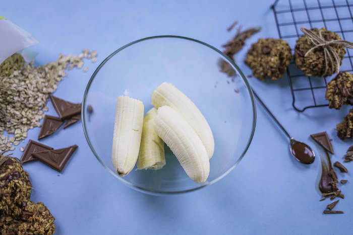 two bananas, in a glass bowl, chewy chocolate chip cookies, on a blue table, chocolate pieces, around it