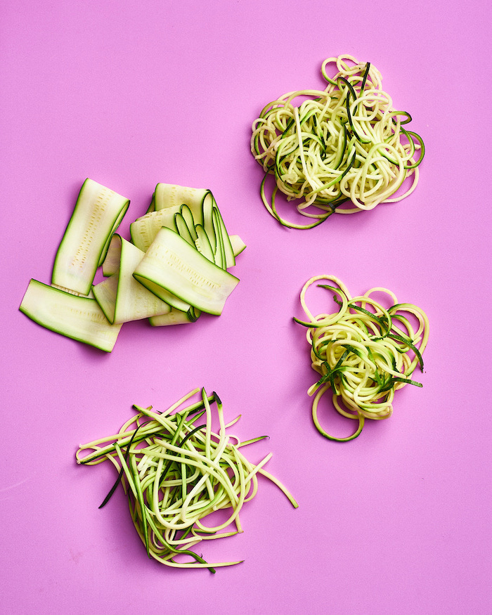 how to make zoodles, four different ways, zucchini noodles, pink background