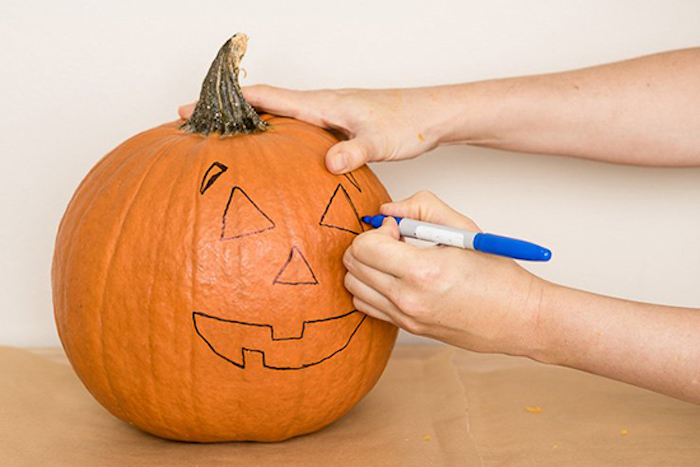 scary pumpkin faces, tracing a face, onto a pumpkin, with a sharpie, white wall