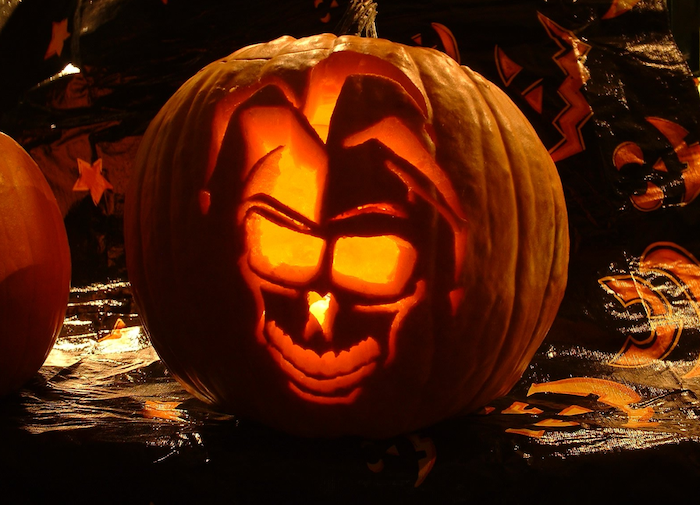 skull of a jester, carved into a pumpkin, lit by a candle, scary pumpkin carvings
