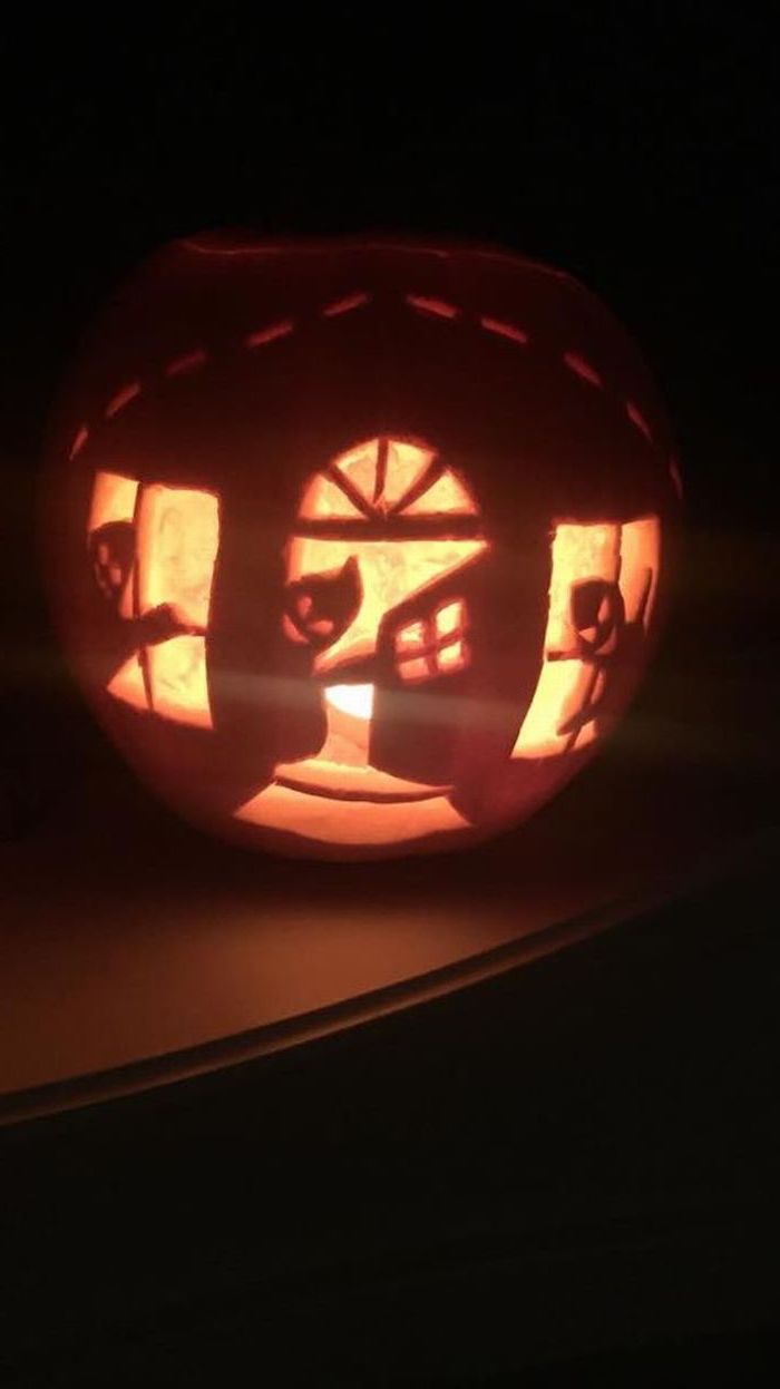 ghosts inside a house, carved into a pumpkin, scary pumpkin carvings, lit by candles, black background
