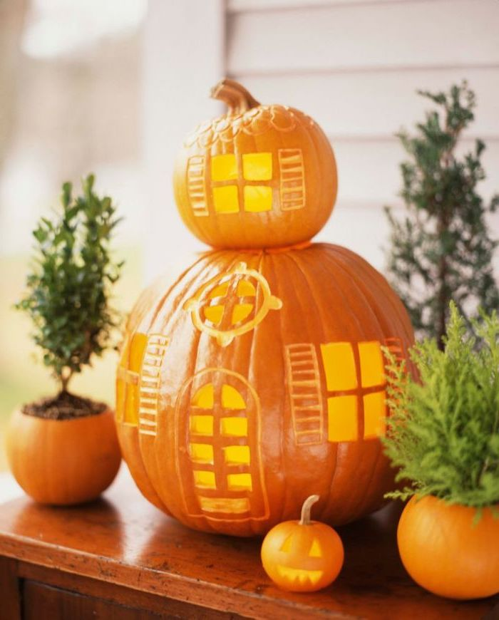 two pumpkins, stacked together, in the shape of a house, scary pumpkin faces, wooden table, potted plants
