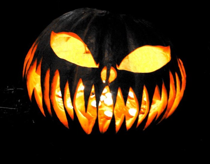 cool pumpkin carvings, large pumpkin, painted in black, lit by a candle, black background