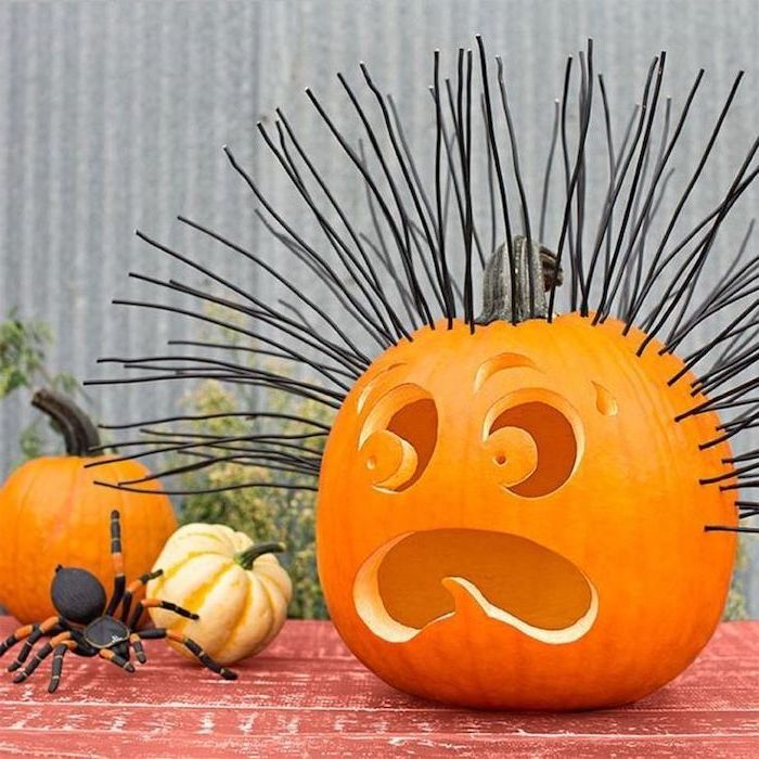 black wooden skewers, nailed to a pumpkin, unique pumpkin carving ideas, large plastic spider, red table