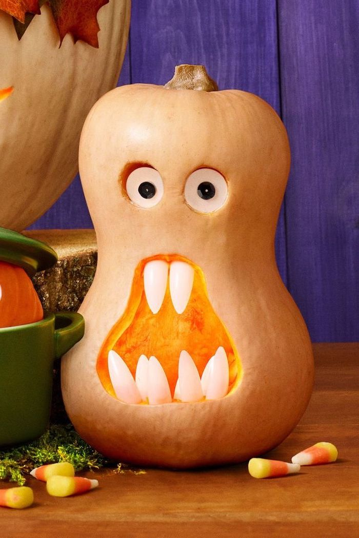 pumpkin with plastic eyes, with plastic teeth, cool pumpkin carvings, interesting shape, on a wooden table