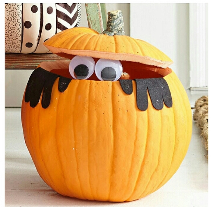 pumpkin with the top cut out, two plastic eyes, felt black arms, glued to it, unique pumpkin carving ideas