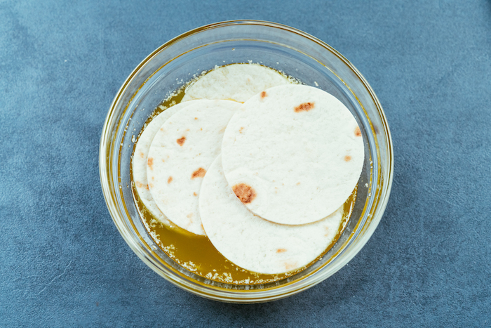 tortilla wraps, soaked in butter, how to make tacos, glass bowl, blue table
