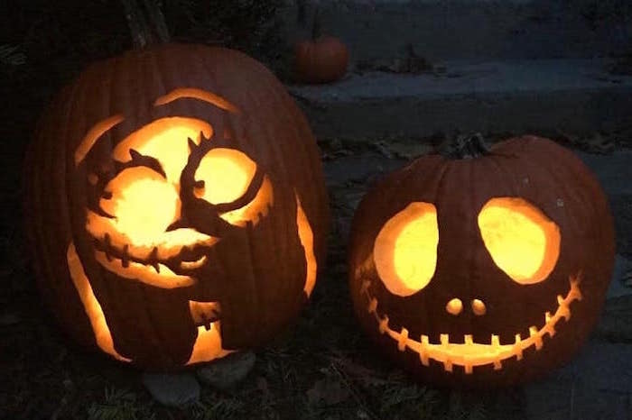 jack skellington and sally, nightmare before christmas inspired, funny pumpkin carving ideas, lit by candles