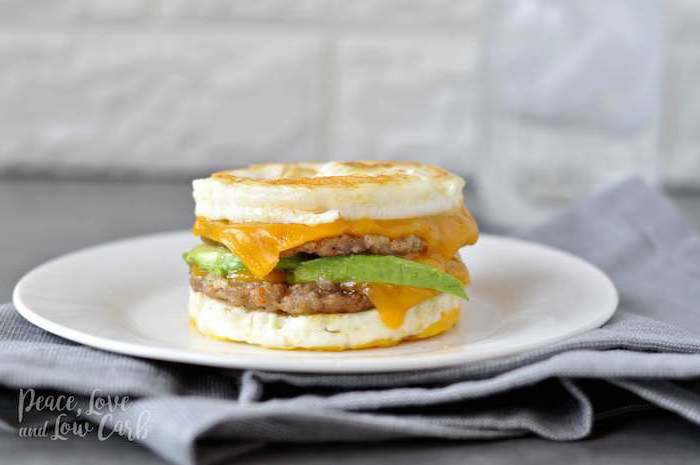 egg sandwich, with ground beef, cheese and avocado, low carb breakfast without eggs, white plate, grey cloth