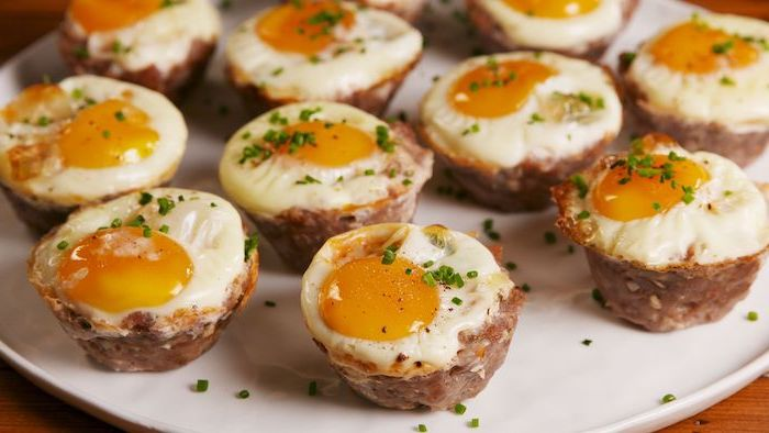 sausage and egg, cheese muffins, low carb breakfast without eggs, arranged on white plate, chives on top
