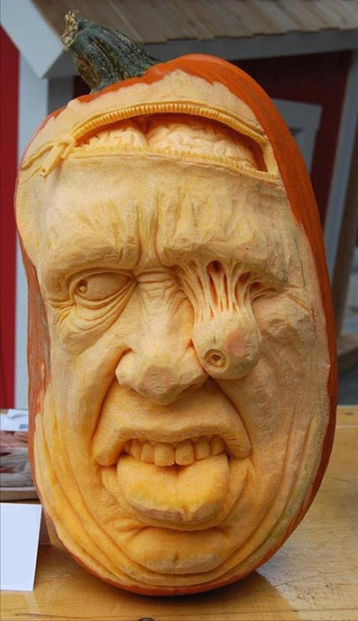man's face, carved into a pumpkin, falling eye, brains coming out, funny pumpkin carving ideas, wooden table