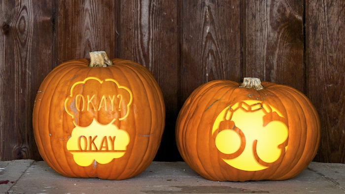 two pumpkins, with different carvings, funny pumpkin carving ideas, wooden background