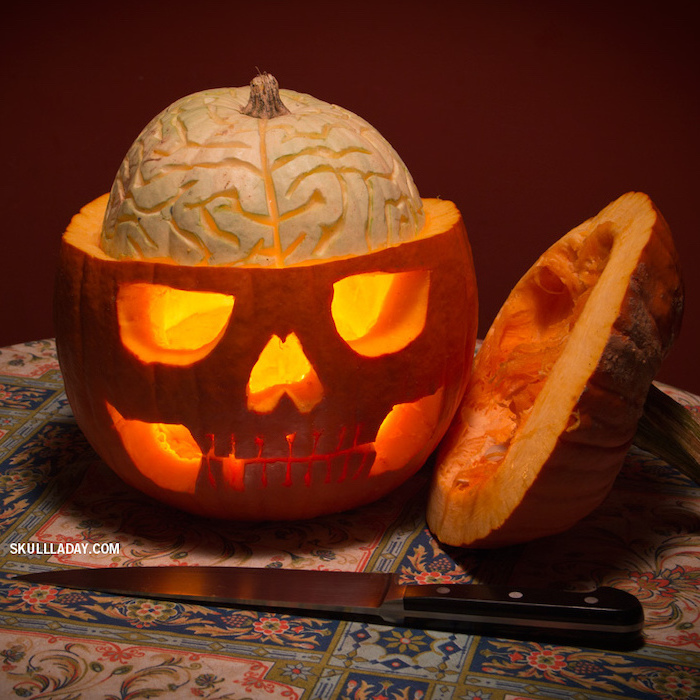 skull carved into a pumpkin, top removed, brains coming out, funny pumpkin carving ideas, colorful cloth