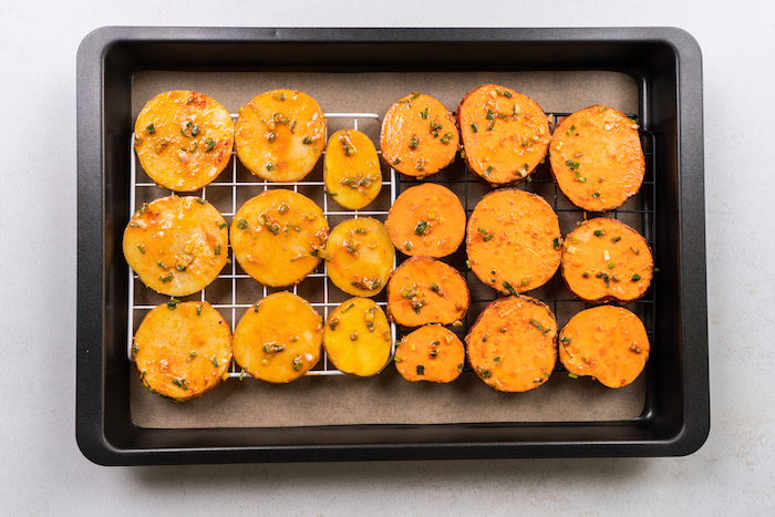 potato and sweet potato slices, arranged on metal rail, homemade potato chips recipe, in paper lined baking sheet