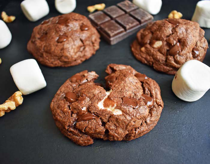 cocoa cookies, marshmallows inside, split in half, marshmallows scattered around, black table, chocolate chunk cookies