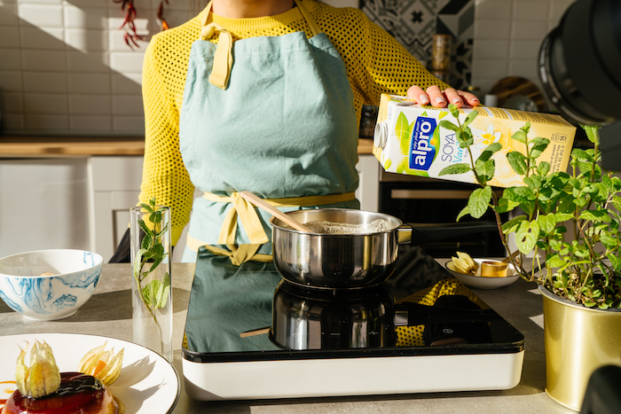 woman wearing yellow sweater and blue apron, pouring soya milk in pot over hot plate, creme caramel recipe