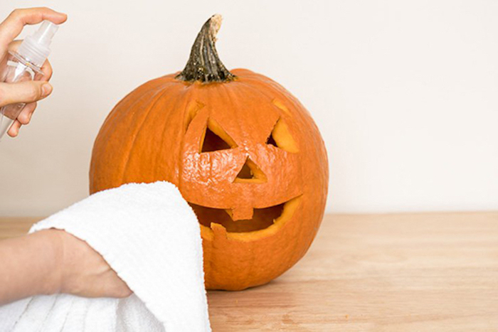 spraying the pumpkin, scary pumpkin faces, white towel, wooden table, white wall