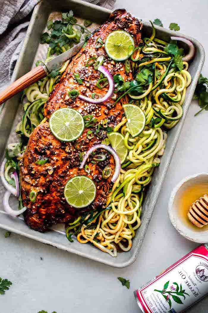 baked salmon, sriracha glazed, lime sliced on top, zoodles on the side, making zucchini noodles