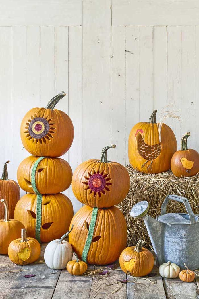 lots of pumpkins, stacked together, pumpkin carving designs, wooden background, hay stacks, metal bucket