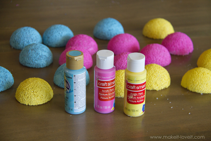 styrofoam balls, cut in half, baby costumes for boys, painted in blue yellow and pink, wooden table