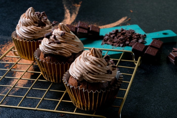 three cupcakes arranged on a rack, chocolate cupcakes recipe, frosting and crumbled chocolate on top