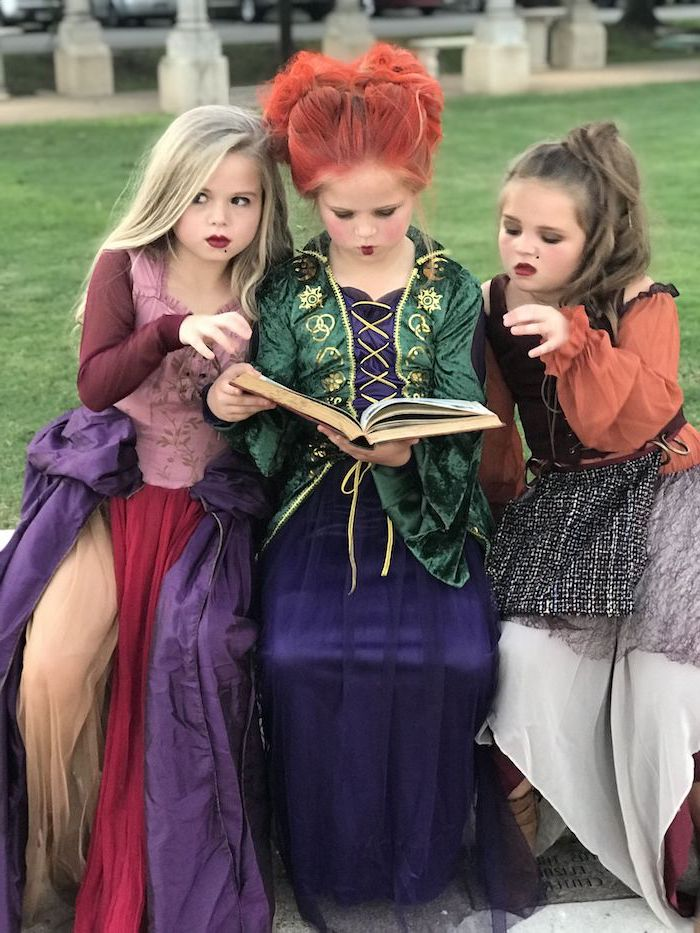 three girl, dressed as witches, hocus pocus movie inspired, twin halloween costumes, long gowns, reading a book