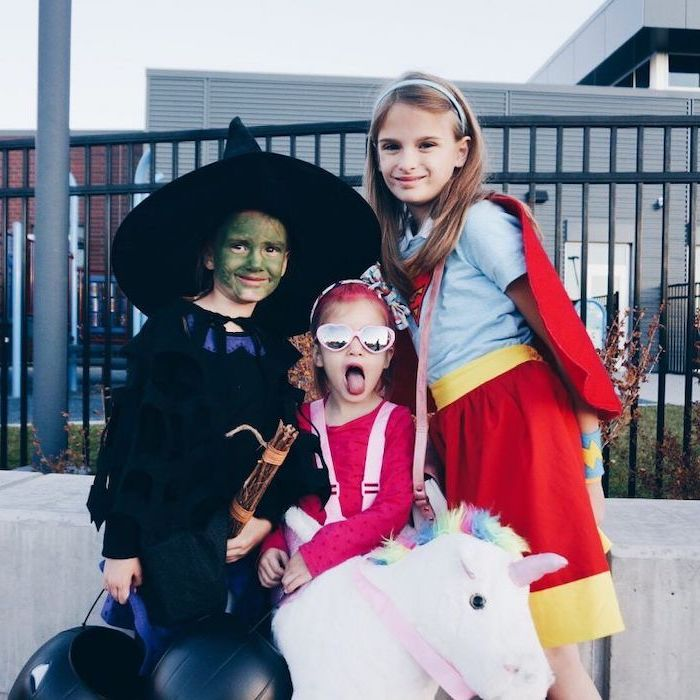 twin halloween costumes, three girls, dressed as a witch, unicorn and supergirl