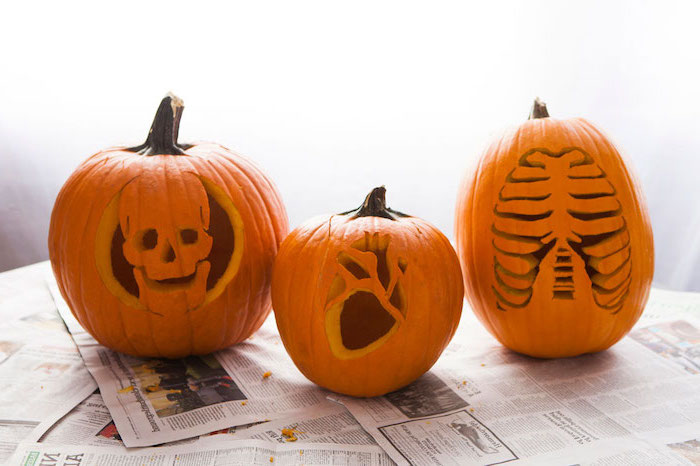 three pumpkins, skull and heart, rib cage, carved into them, pumpkin carving designs, arranged on top of newspapers