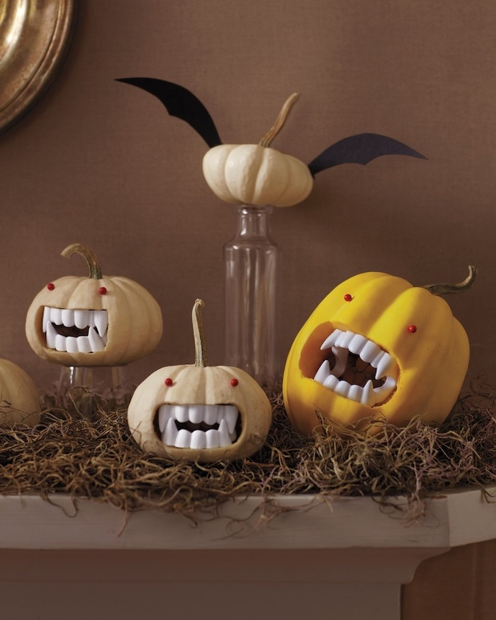 four pumpkins, arranged on a mantle, pumpkin carving designs, plastic vampire teeth, red eyes, glued to them
