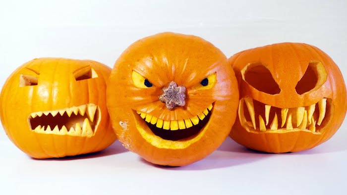 easy pumpkin carving ideas, three pumpkins, scary faces carved into them, white background