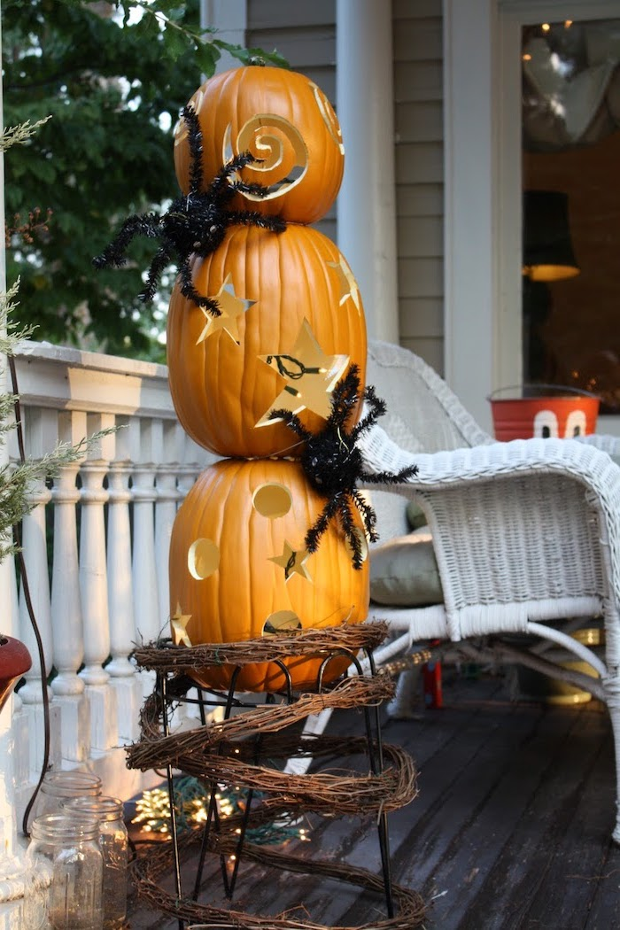 three pumpkins, stacked together, plastic spiders on them, easy pumpkin carving ideas, garden patio, white chair