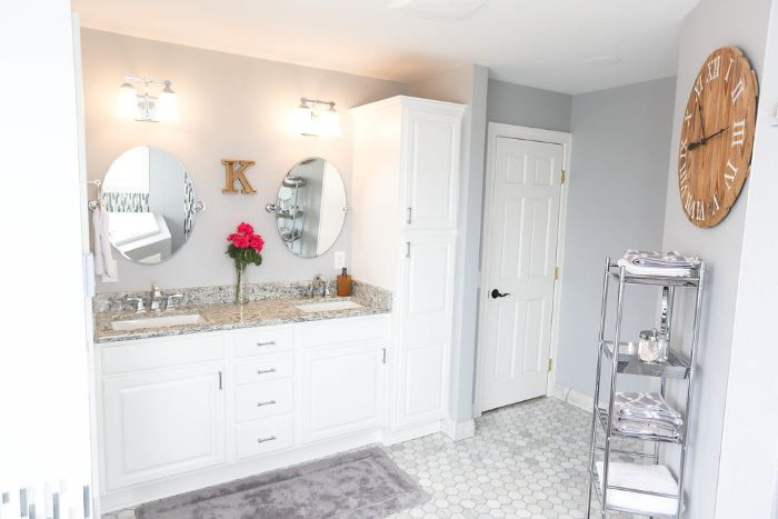 white walls, mosaic floor, tips for your bathroom remodel, two sinks, two mirrors, white vanity, wooden clock