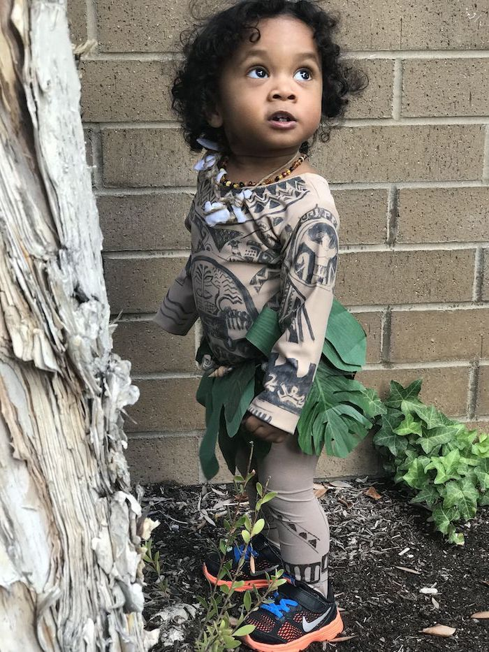 toddler girl halloween costume, dressed as maui, moana movie inspired, black curly hair, brick wall