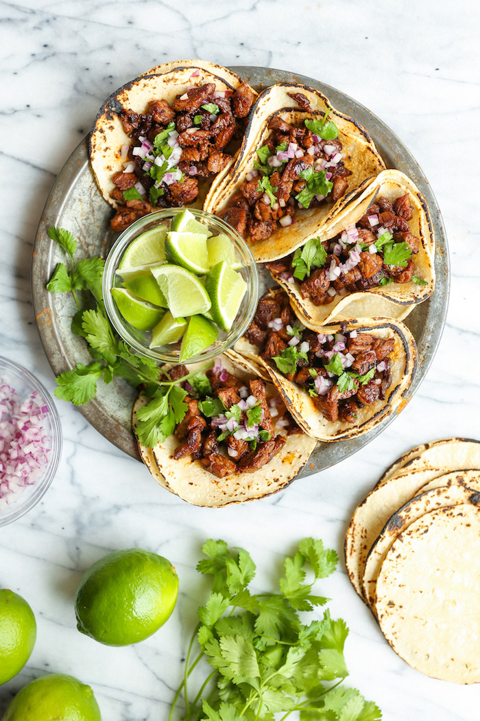 five tacos, tortilla wraps, filled with beef, how to make taco meat, arranged on a silver plate, lime slices, in a glass bowl