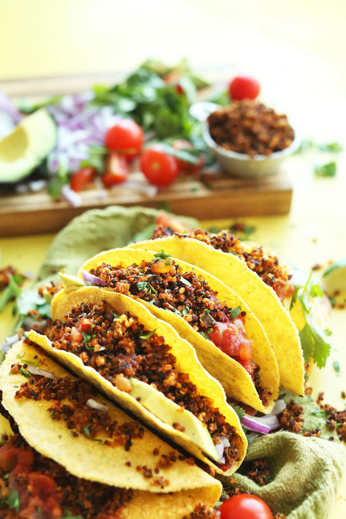 tortilla wraps, filled with salsa, boiled quinoa, taco ingredients, green table cloth, wooden cutting board