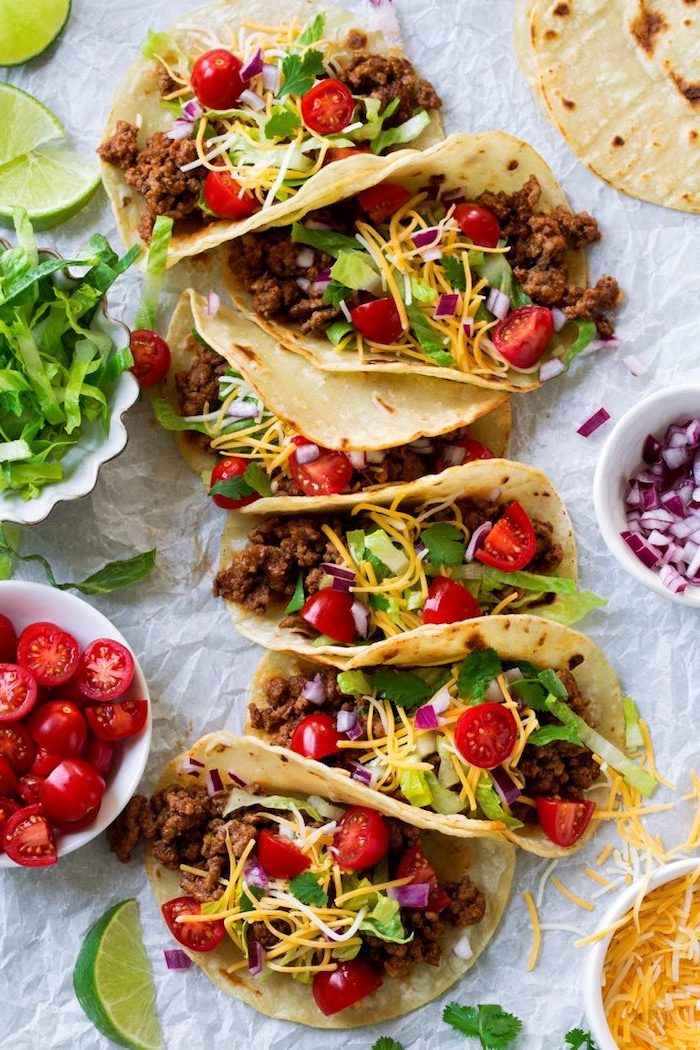 six tacos, how to make taco meat, tortilla wraps, filled with beef, cherry tomatoes, cheese on top, lime slices