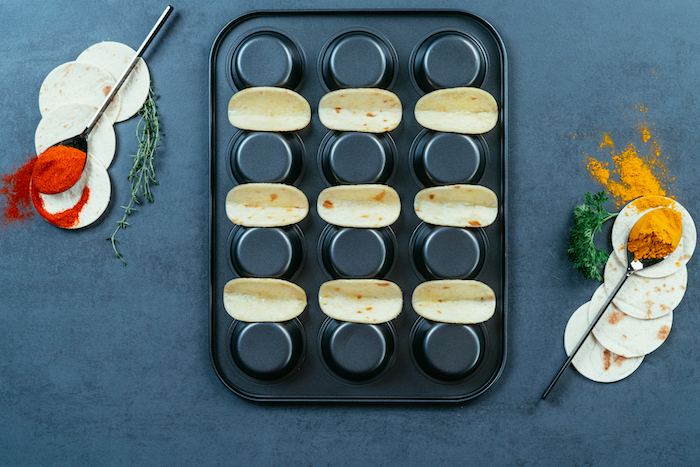tortilla wraps, arranged on a black, baking tray, how to make tacos, black table, spoons with seasoning