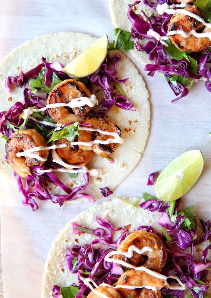 taco ingredients, tortilla wraps, filled with cabbage, fried shrimp, lime slices on the side