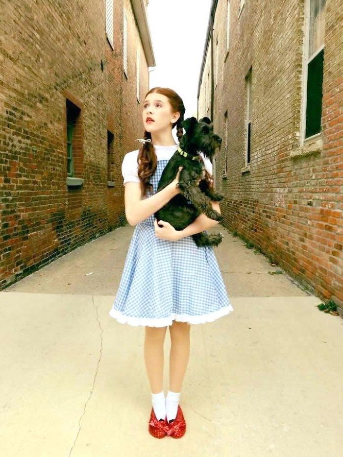 girl dressed as dorothy, wizard of oz inspired, braided hair, red shoes, funny halloween costumes for kids, holding a dog