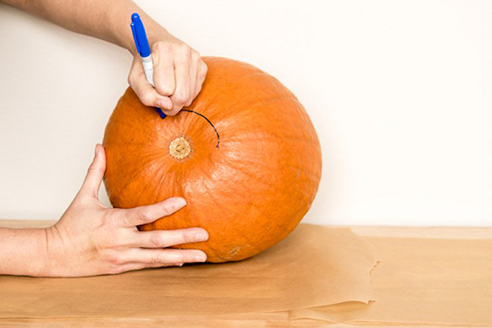 two hands, tracing a line, with a sharpie, onto a pumpkin, on a wooden table, jack o lantern faces, white wall