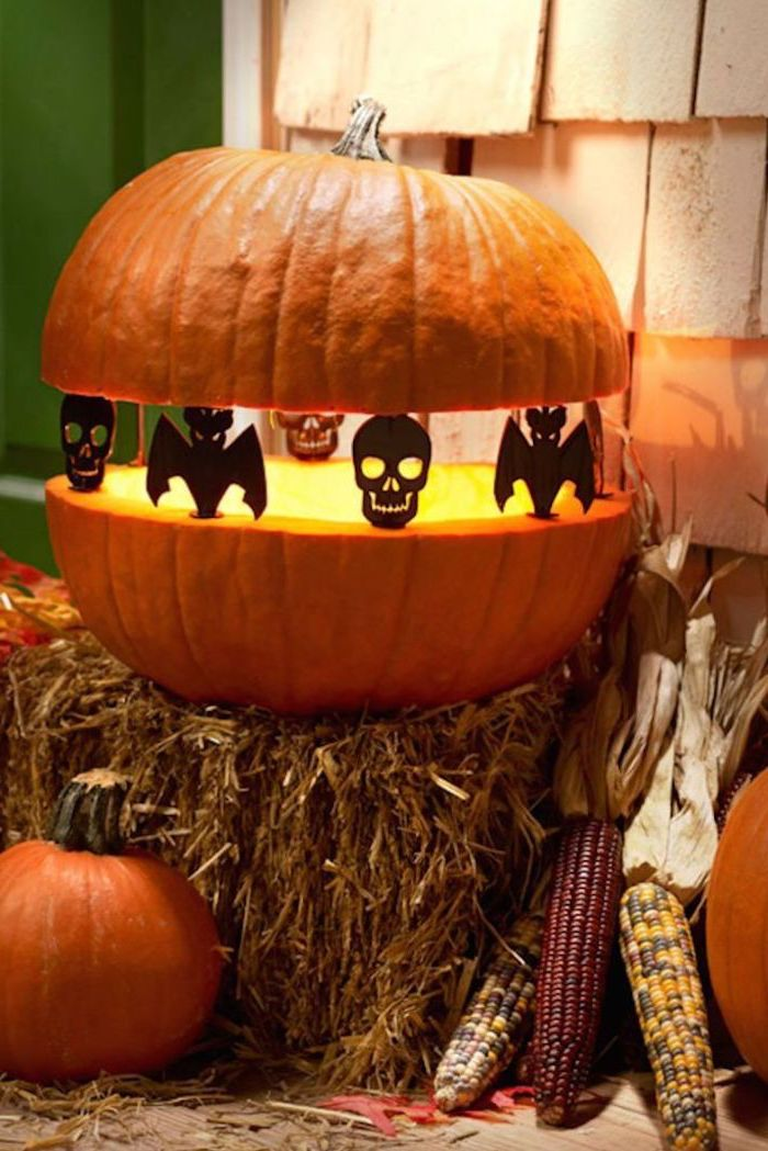 two pieces of a pumpkin, held together by figurines, skulls and bats, pumpkin carving patterns, on top of haystack