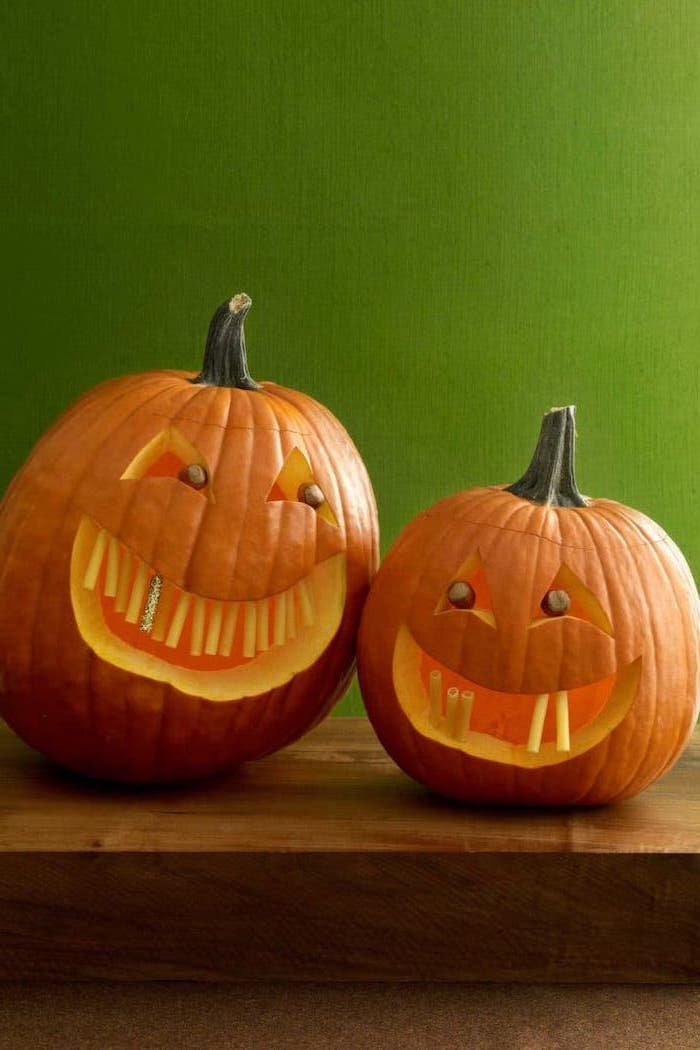 green wall, pumpkin carving patterns, two pumpkins, on a wooden table, pasta for teeth