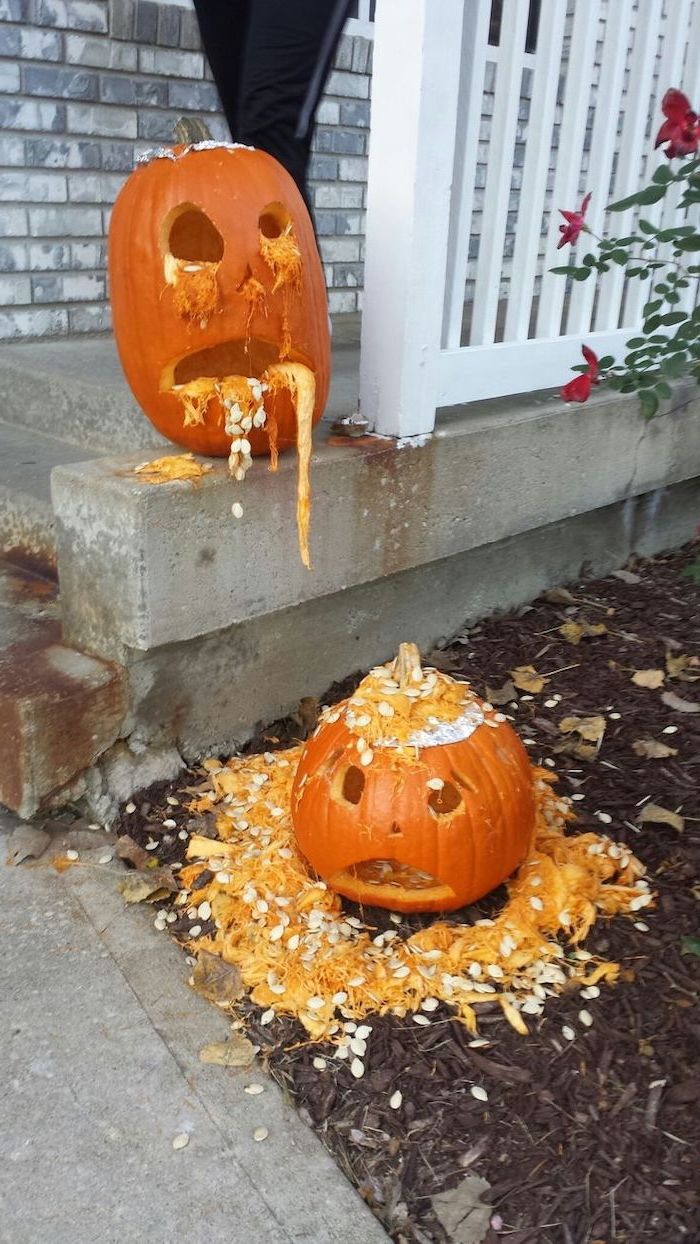 drunk pumpkin, vomiting on top of another, pumpkin carving patterns, white wooden fence, brick wall