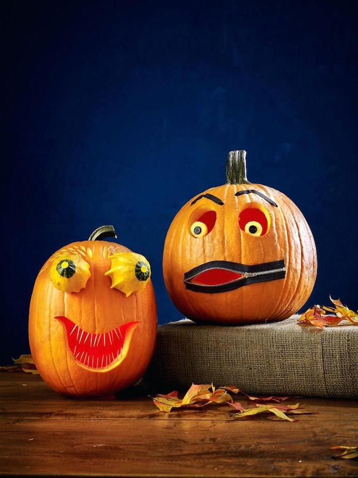 two pumpkins, arranged on a wooden table, with fall leaves, easy pumpkin carving ideas, blue background