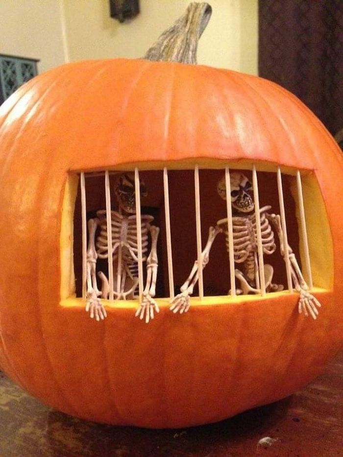 halloween pumpkin carvings, two skeletons, inside the pumpkin, jail bars, made of toothpicks