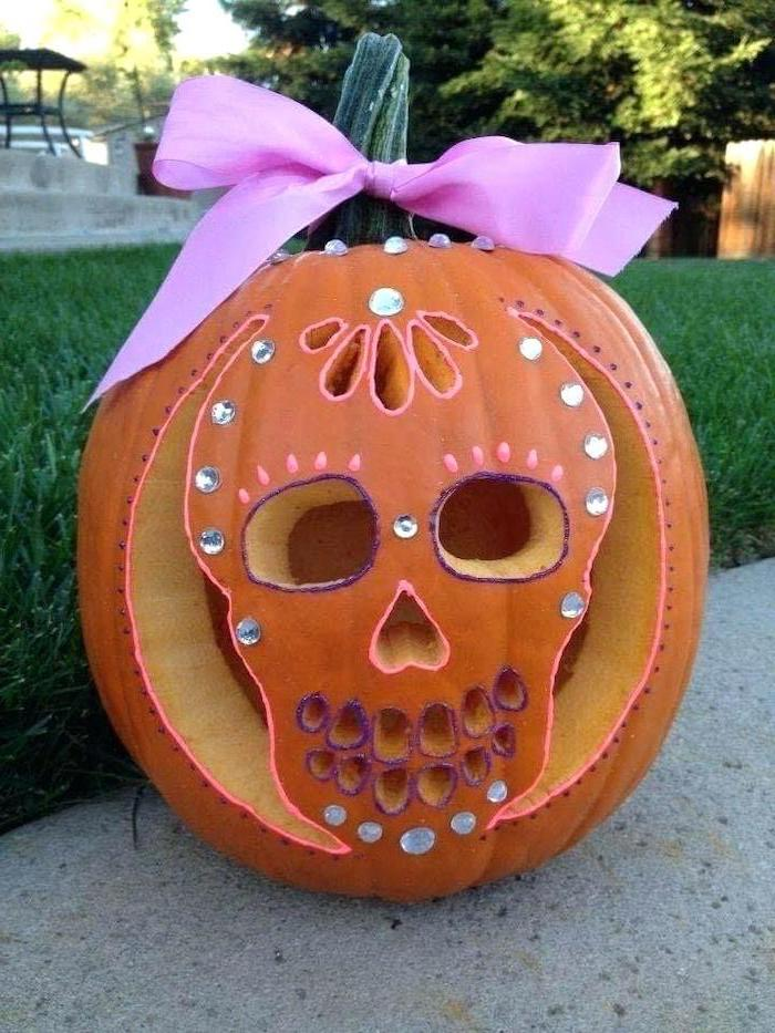 carved pumpkin, with a pink bow, rhinestones glued to it, halloween pumpkin carvings, skull shape