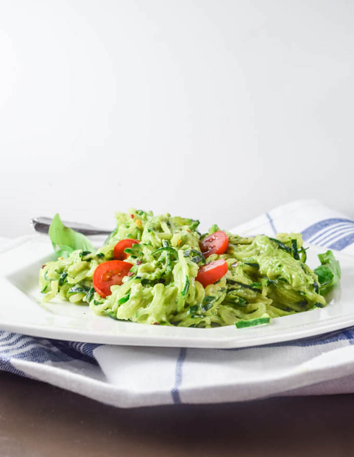 white and blue table cloth, white plate, how to cook zucchini noodles, zoodles with pesto, cherry tomatoes