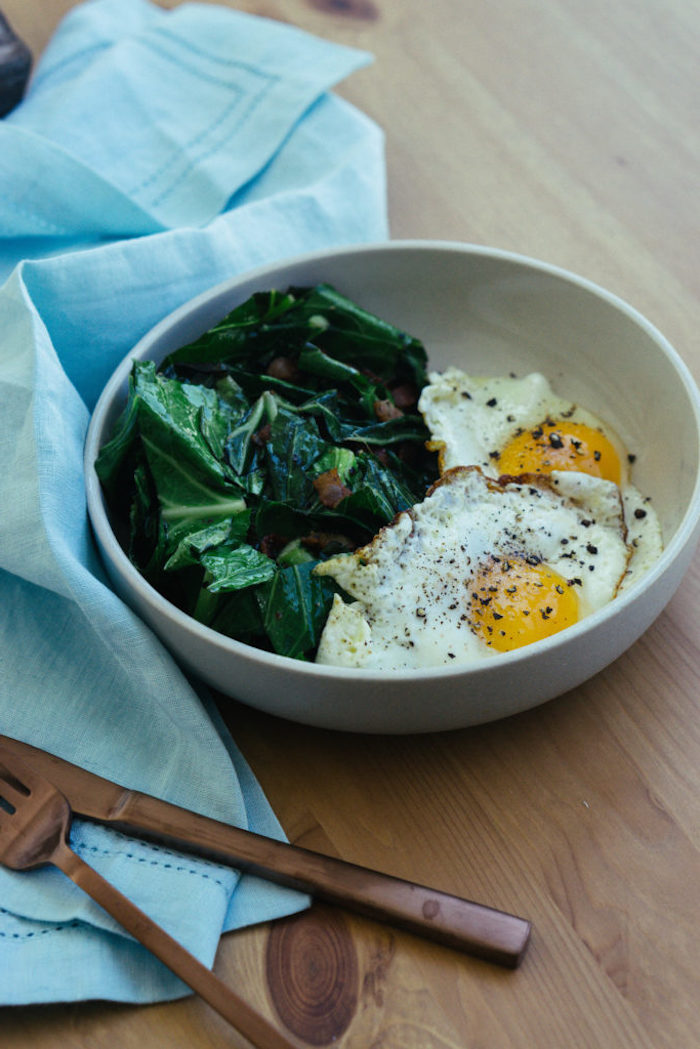 fried eggs, spinach and bacon, on the side, easy keto meals, white bowl, blue table cloth, wooden table