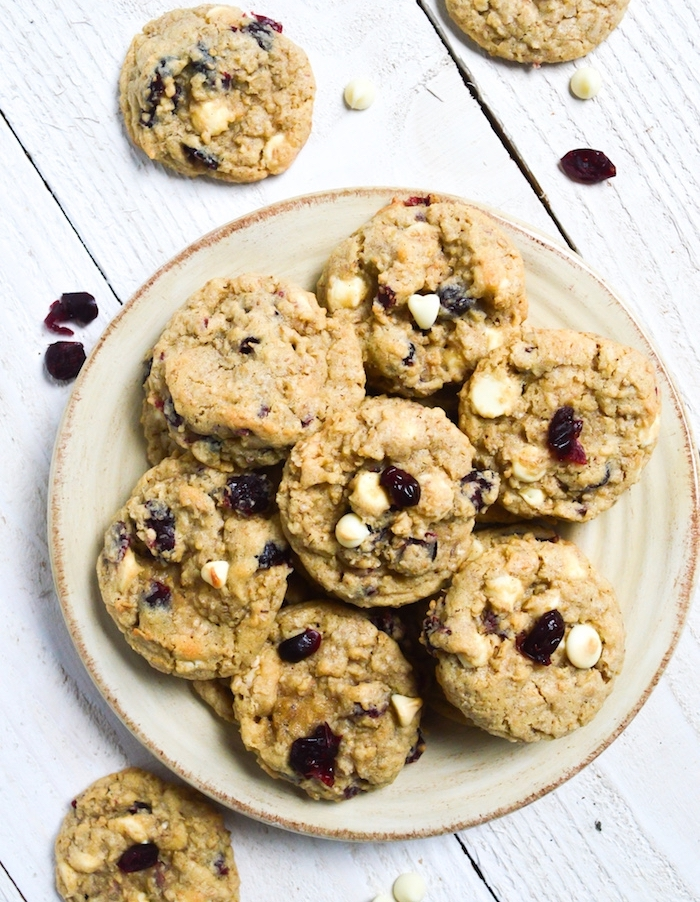 homemade chocolate chip cookies, with raisins, white chocolate chips, in a white plate, white wooden table